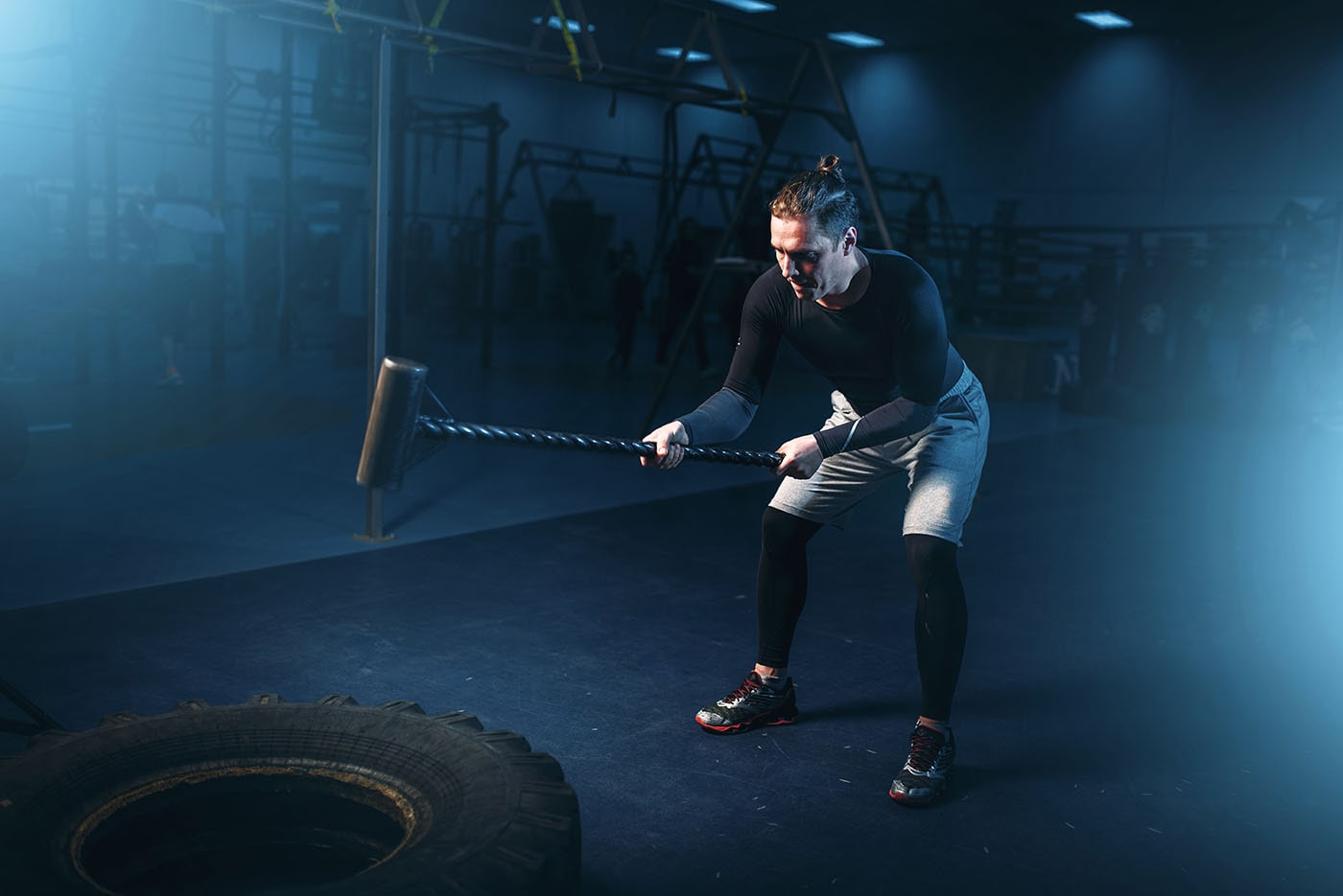 training in gym man with sledgehammer hits tire PC3UH98 min